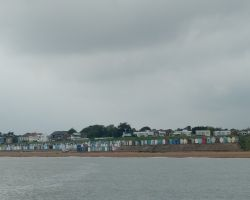 Passing close offshore past TheSouthwold Beach Huts